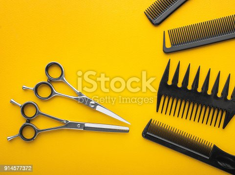 istock scissors and combs on yellow background top view 914577372