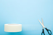istock Scissors and white roll of mesh for split or seam on wall or ceiling on light blue table background. Pastel color. Closeup. Empty place for text. Top down view. 1219375908