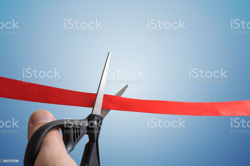Scissors are cutting red ribbon. Opening ceremony concept. Isolated on blue background. stock photo