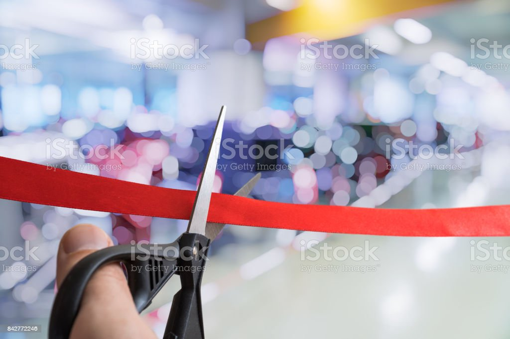 Scissors are cutting red ribbon. Opening ceremony or event. stock photo