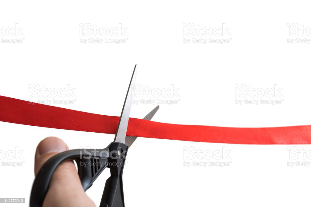 Scissors are cutting red ribbon. Opening event concept. Isolated on white background. stock photo