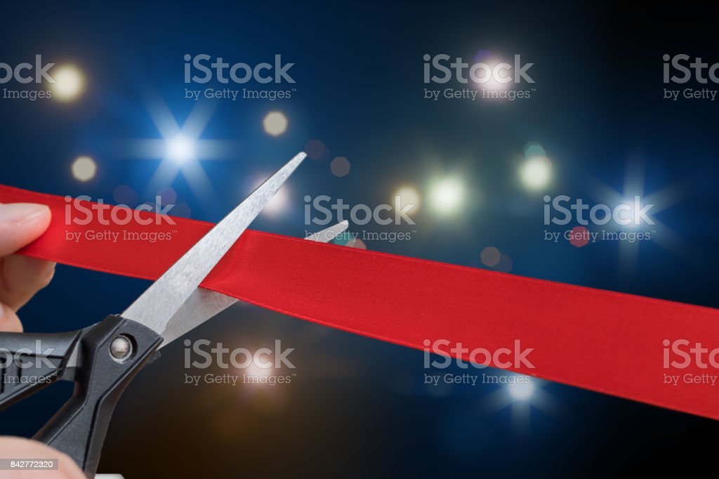 Scissors are cutting red ribbon or tape. Flashing lights in background. stock photo