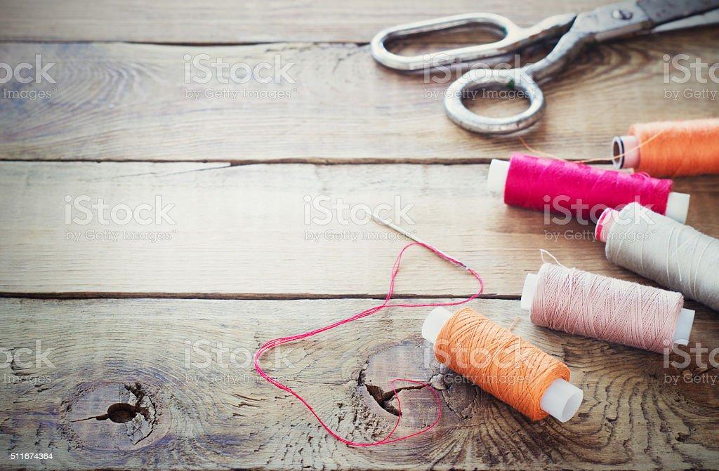 Scissors, bobbins with thread and needles. stock photo