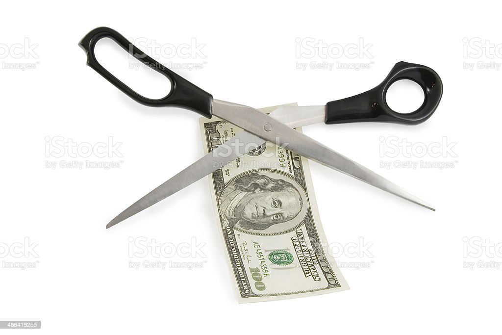 scissors cutting a 100 dollars banknote royalty-free stock photo
