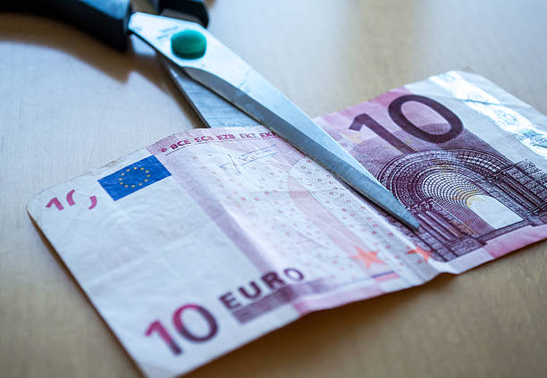 Scissors Cutting a Ten Euro (EUR) Banknote Close Up stock photo