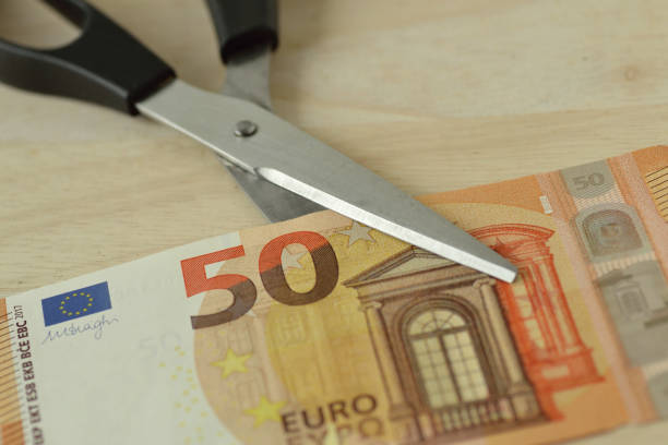 Scissors cutting euro banknote - Concept of reducing cost, price cutting Scissors cutting euro banknote - Concept of reducing cost, price cutting depreciation stock pictures, royalty-free photos & images