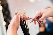 Close Up Of Hairdresser Hands Cutting Costumer Hair.