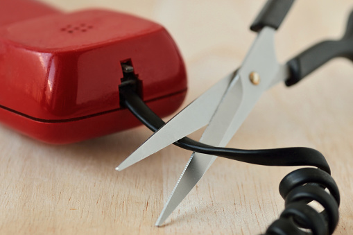 istock Scissors cutting telephone cord - Concept of landline phone 1151430004