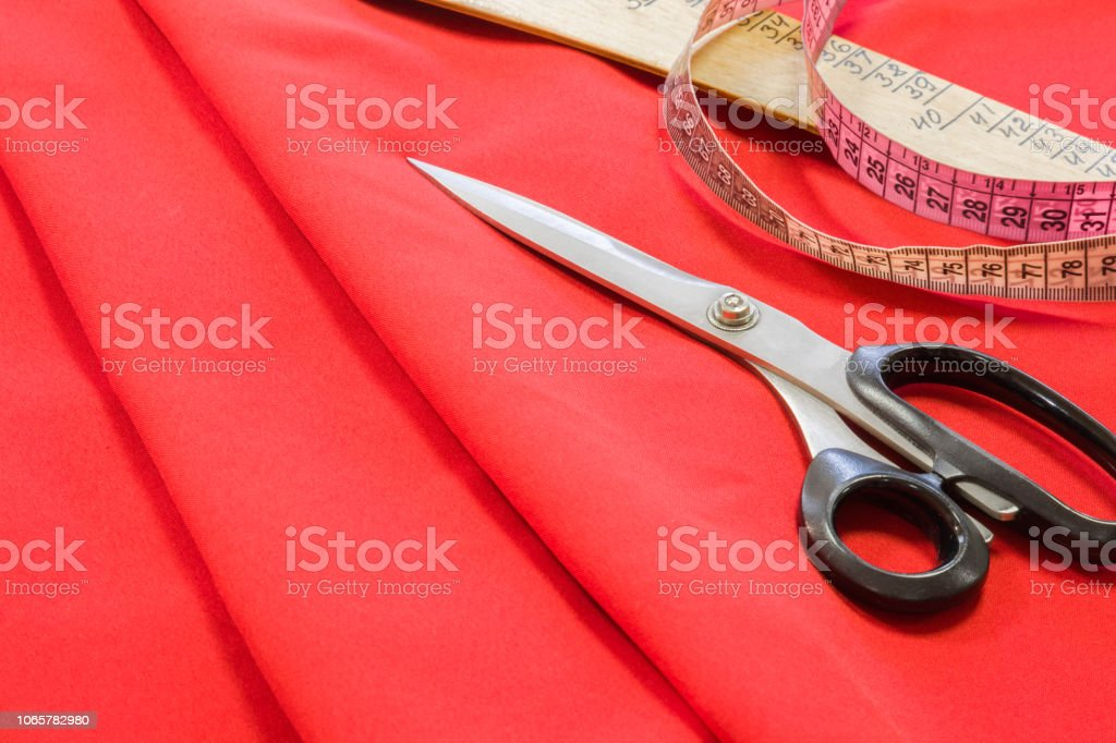 Scissors, measuring tape and ruler on bright red fabric. Handmade...
