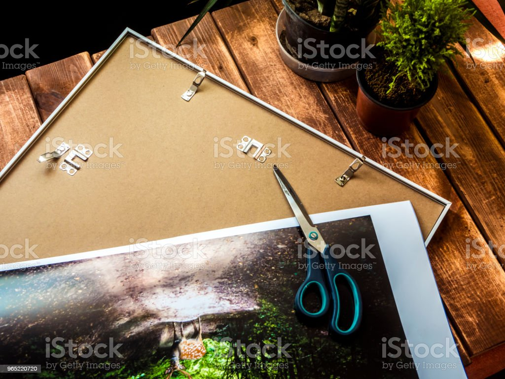scissors on a photo before putting it into a frame overhead view royalty-free stock photo