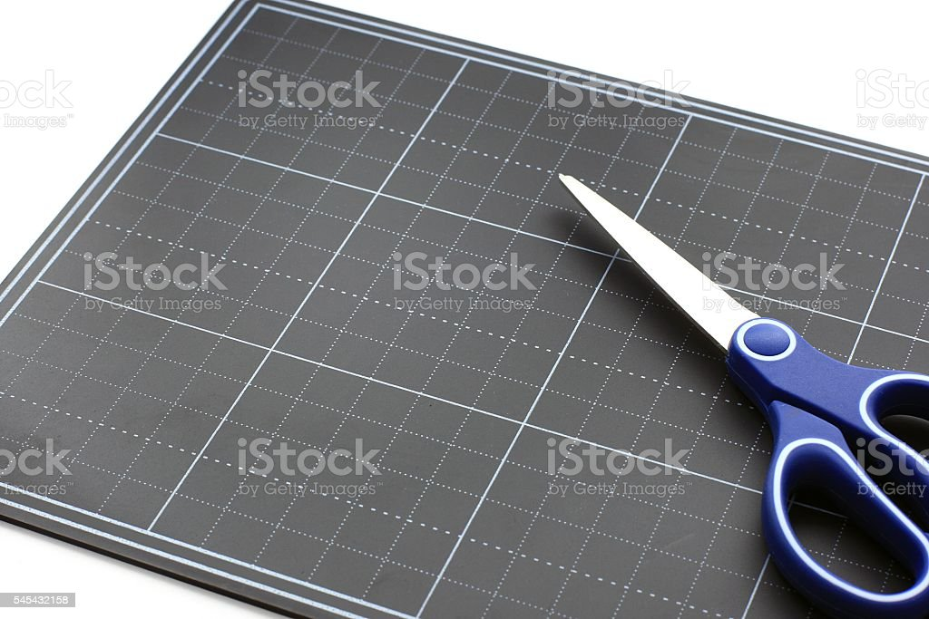 Scissors on the Black paper cutting mat stock photo