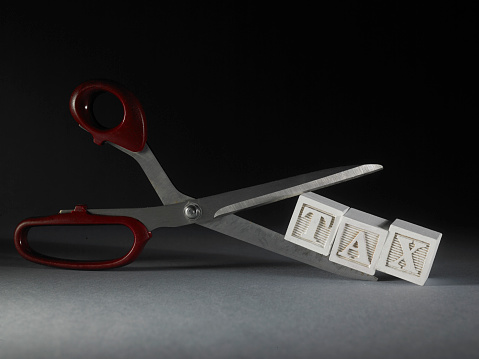 scissors on toy blocks with single word tax on black background