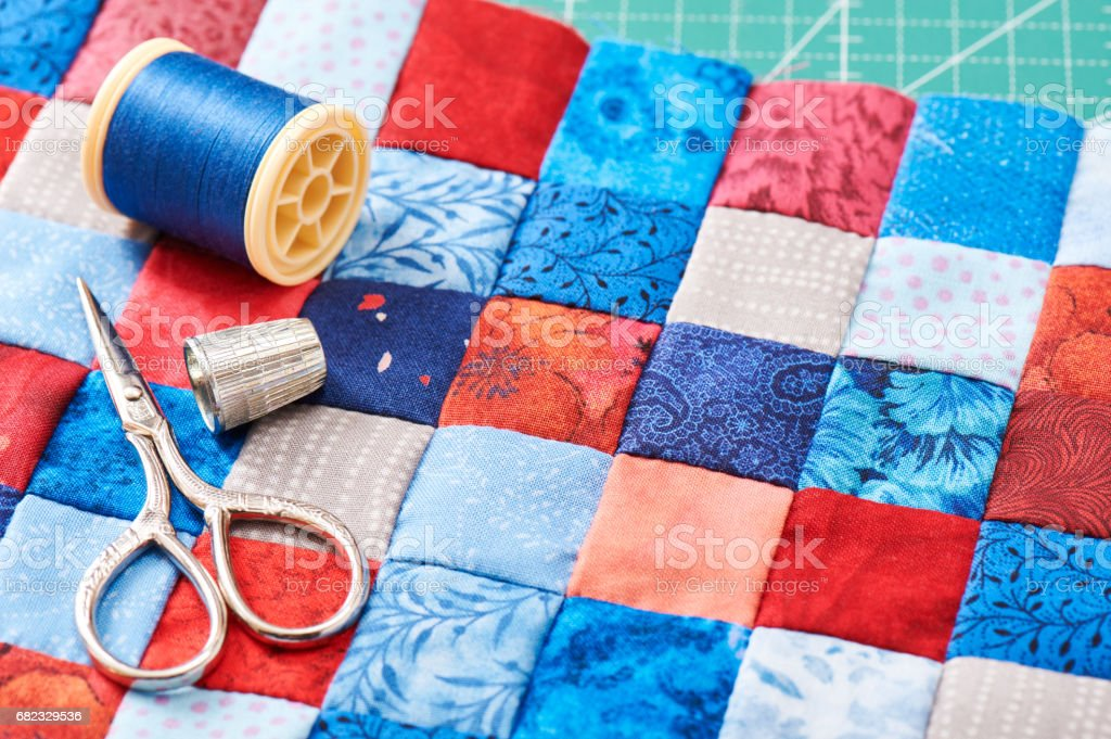 Scissors, thread and thimble lying on blue and red square pieces of fabric sewn together stock photo