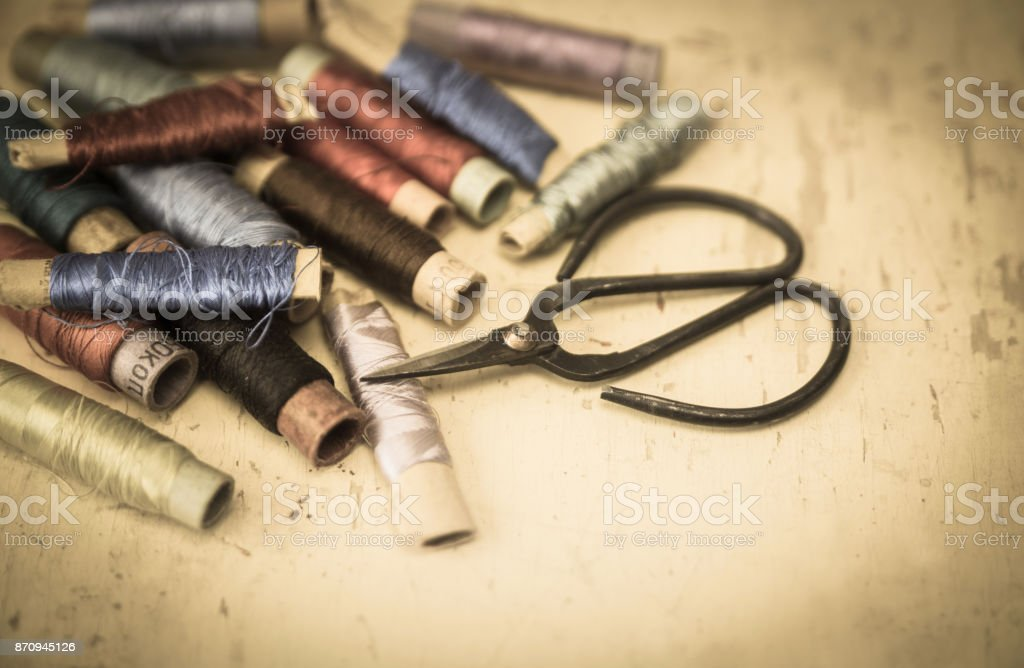 Scissors with silk threads for embroidering on vintage background stock photo