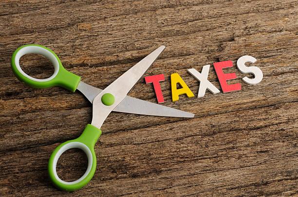 Schere mit Steuern Wort auf einem hölzernen Hintergrund – Foto