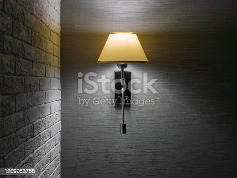 Classic sconce with turned on bulb under lampshade hanging on wall with gray wallpaper next to brick wall. Copy space
