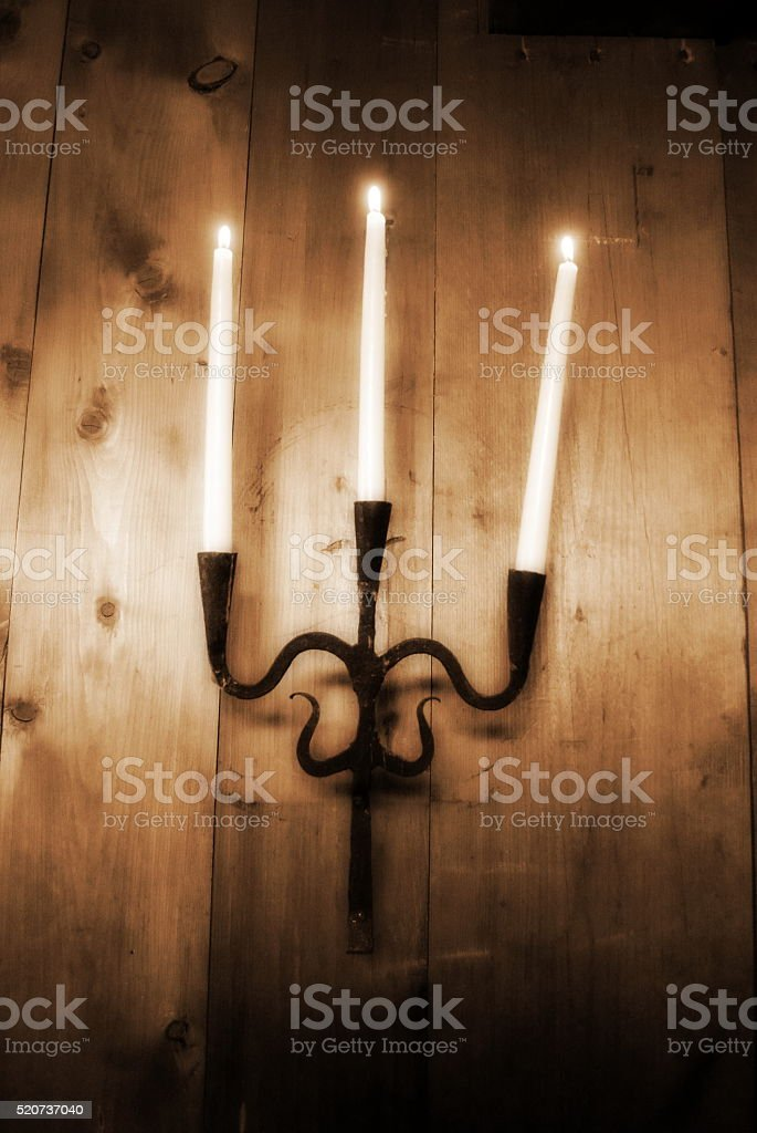 Sconce/Candelabra with three lit candles stock photo