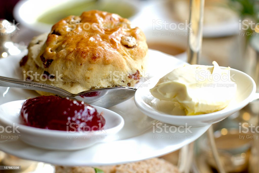 Scone, Clotted Cream and Jam for High Tea Fancy scone with clotted cream and jam for English style High Tea, shallow depth of field, focus on front of scone.  This image was taken in York, England at a fancy tea house. Afternoon Tea Stock Photo