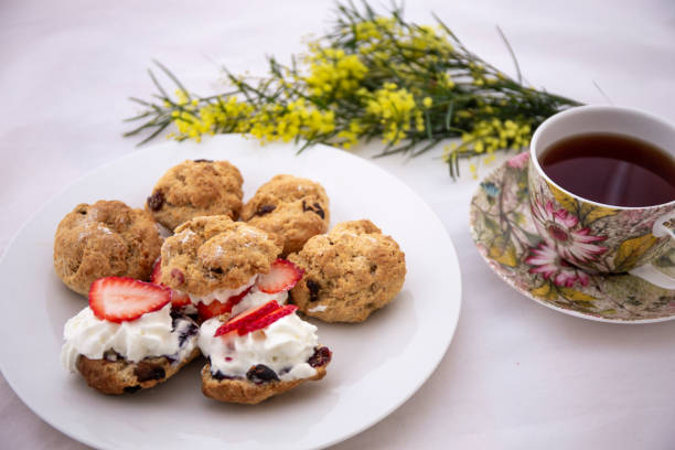 scones with cream and jam served with tea - mimosa cake foto e immagini stock