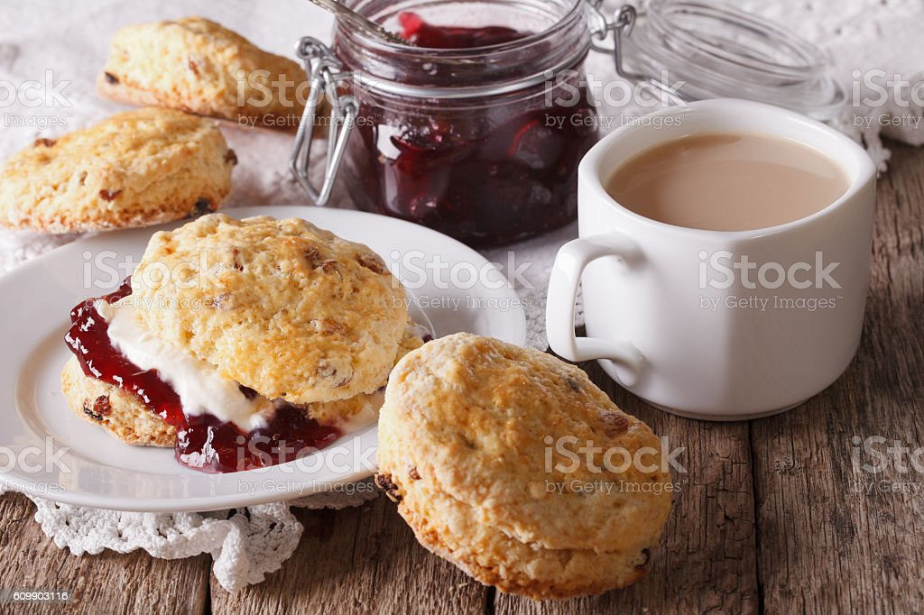 Scones with jam and tea with milk on the table - foto de acervo