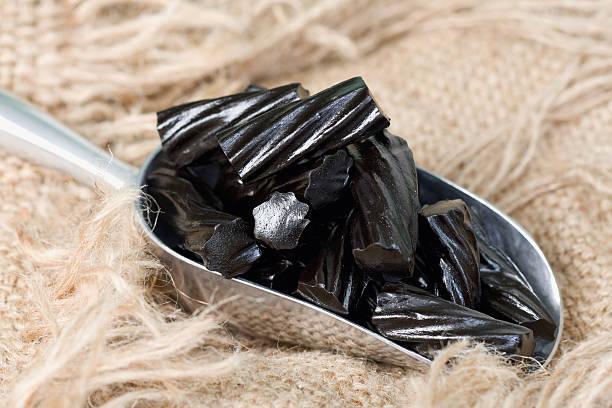 pallina di liquorice di zucchero nero in iuta - liquirizia foto e immagini stock