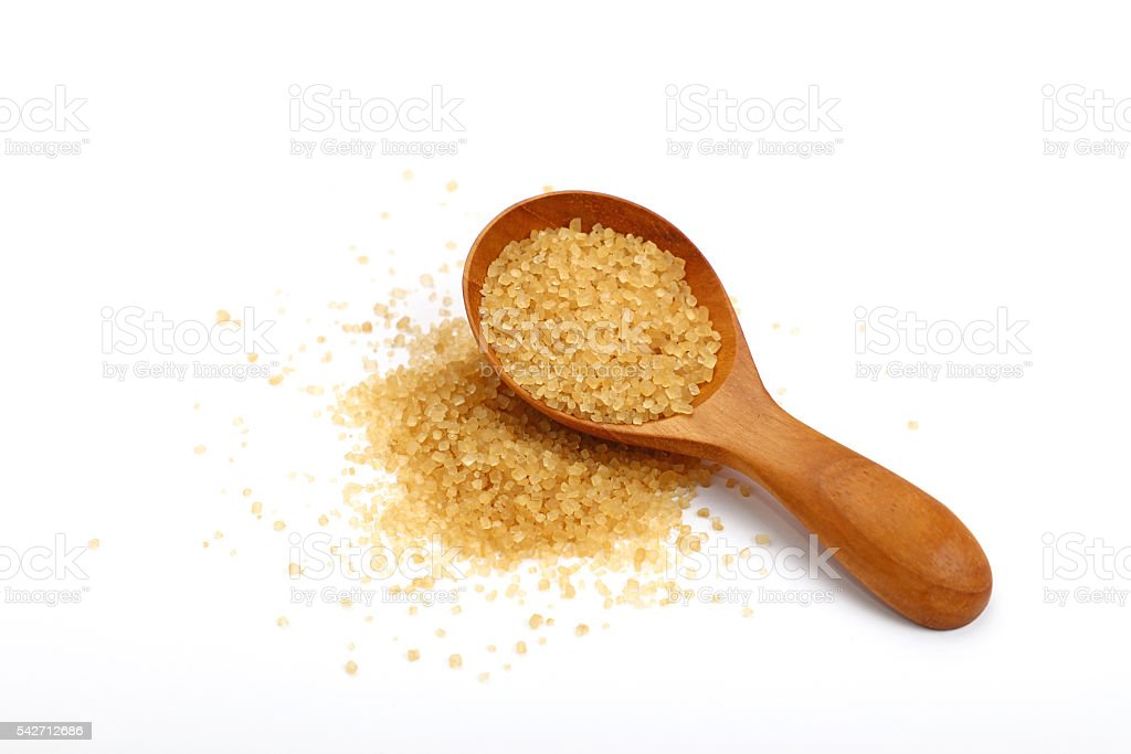 Scoop of brown cane sugar isolated on white stock photo