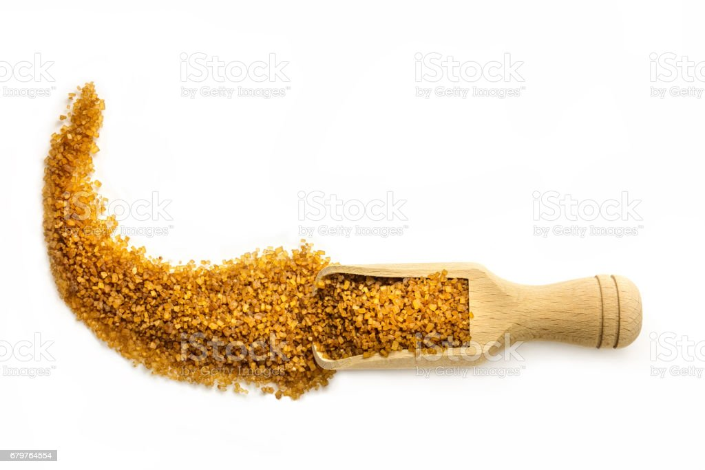 Scoop of brown sugar on white with copyspace, overhead shot stock photo