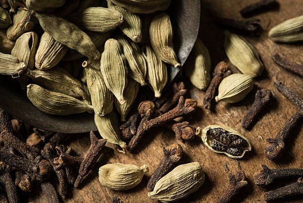 Scoop of Cardamom and Cloves An antique scoop tin scoop filled with cardamom seeds and cloves on a rustic wooden surface. cardamom stock pictures, royalty-free photos & images