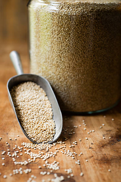 Scoop of Quinoa Next to a Glass Jar A kitchen scoop full of quinoa laying on a rustic wood surface next to a glass jar filled with quinoa. quinoa stock pictures, royalty-free photos & images