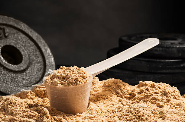 Scoop of whey protein on black background. Chocolate flawour Product photograph of spoon or measuring scoop of whey protein on black chalkboard background protein stock pictures, royalty-free photos & images