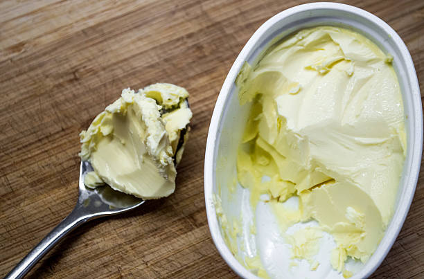 Scooping Butter/Margarine from a Tub High-angle View stock photo