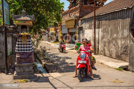 Bali, Indonesia - December 01, 2019: Traditional Balinese Tribe Village. Scooter drivers wait on crossroads. Scooter is a popular balinese transport