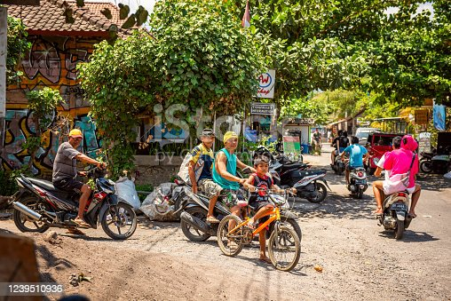 Bali, Indonesia - December 01, 2019: balinese road traffic, scooter drivers wait on crossroads. Scooter is a popular balinese transport