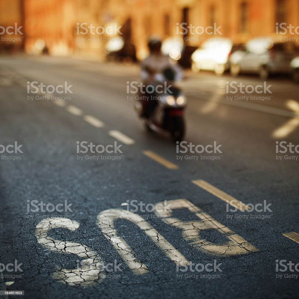 Scooter Driving in a City Street, Tilt Shift, Bus Stop royalty-free stock photo