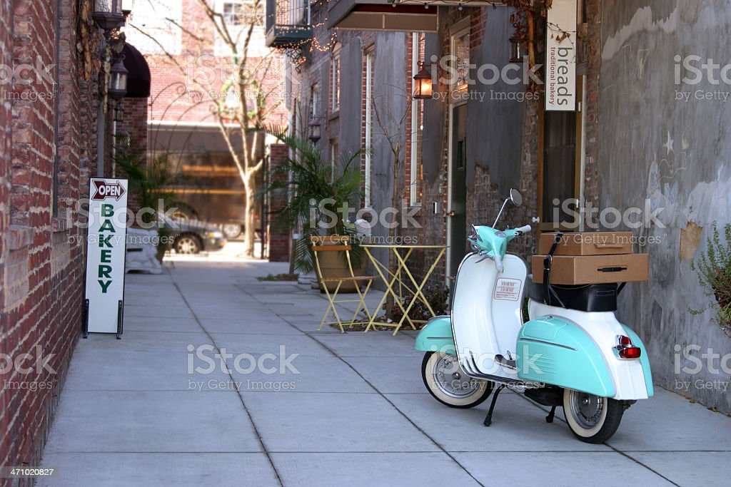 Scooter in alley beside bakery stock photo