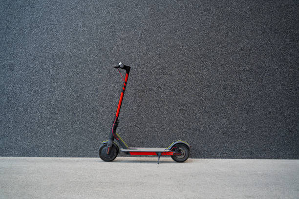 e scooter next to black wall - electric push scooter stock photos and pictures
