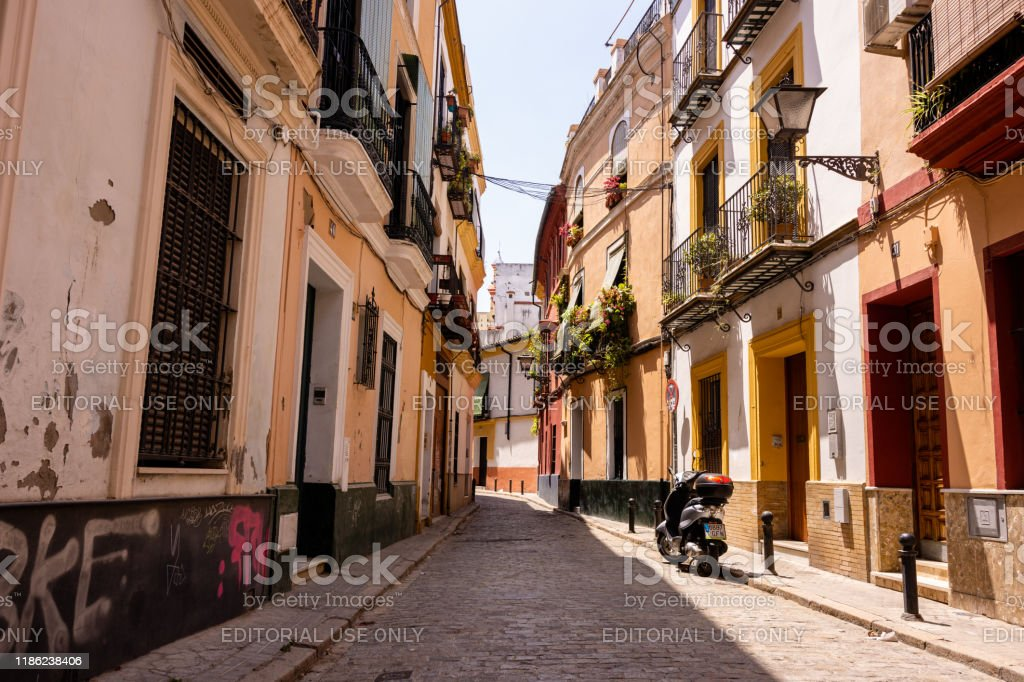 Scooter parked in cobblestone street with graffiti in Seville, Spain - Royalty-free Ancient Stock Photo