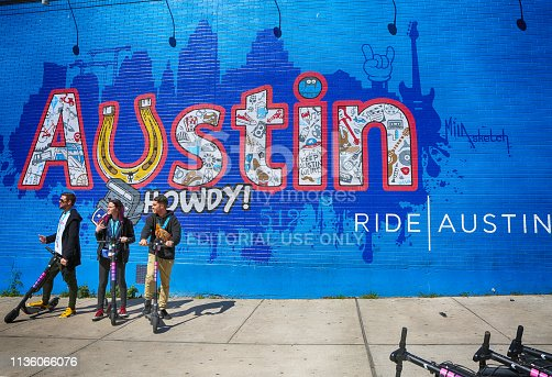 Austin, Texas, March 14, 2019, SXSW South by Southwest Annual music, film, and interactive conference and festival. Members of SXSW in front of wall painting at 6th street, using electric scooter-popular transportation in city.