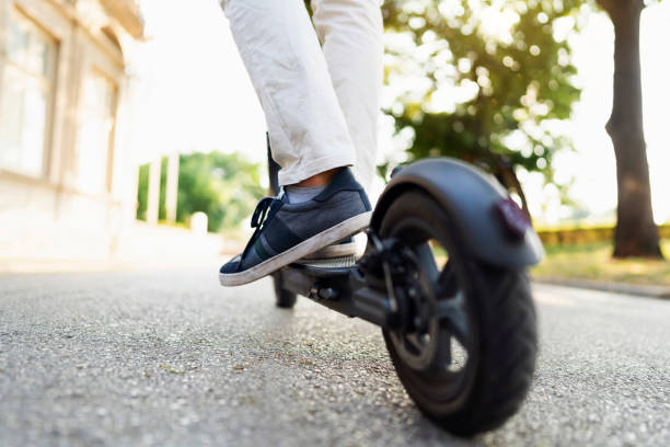 scooting around town - electric push scooter stock photos and pictures
