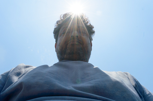 Scorching Hot summer sunlight rays falling human head. Man looks down on sun light heat temperature. Protection from ultraviolet light and sunburn background.  Sunstroke, heatstroke, greenhouse effect