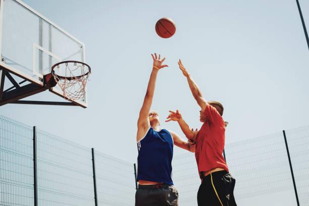 score pour trois dans le jeu de basket-ball - samen sporten stockfoto's en -beelden