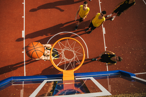Drone point view of Young basketball player scoring with slum dank, close up to basketball hoop