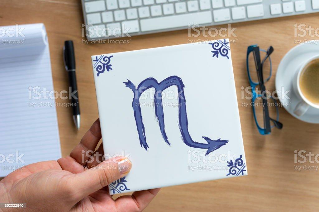 scorpio Delfts Blue zodiac tile above working desk stock photo