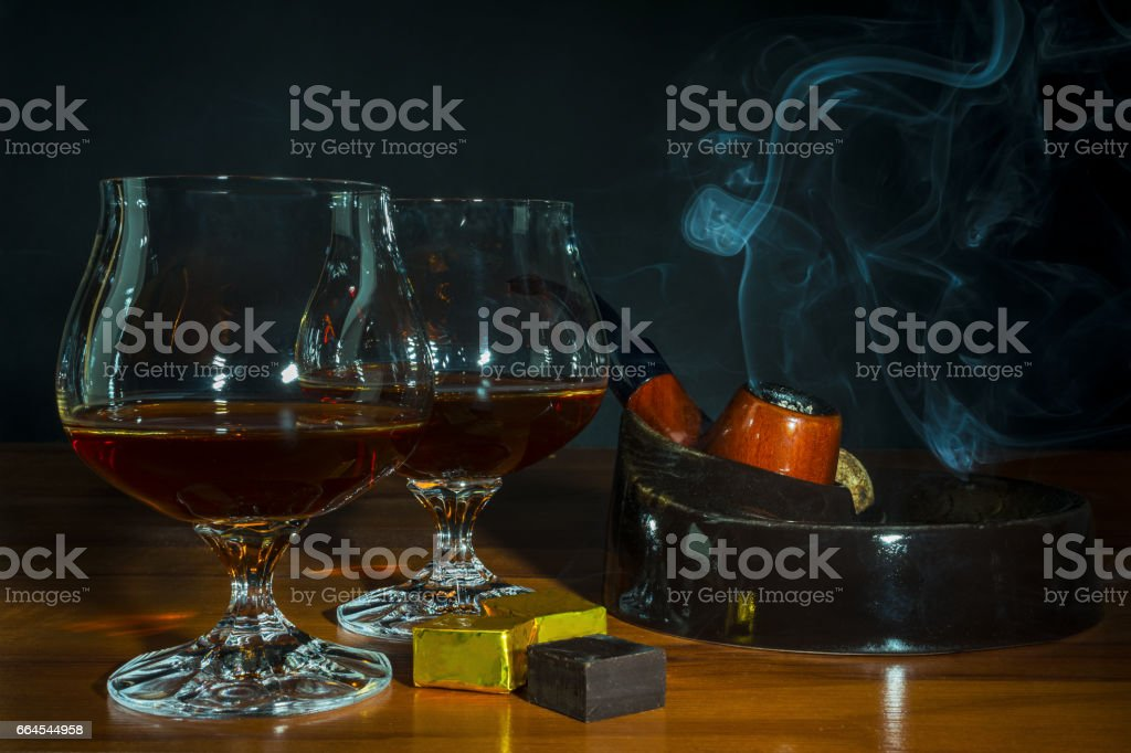 Scotch drink and tobacco pipe with smoke on black background royalty-free stock photo