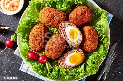 scotch eggs, boiled eggs wrapped in minced sausage, served with lettuce and radish on a plate on a grey concrete table with a bowl of mayonnaise paprika sauce, view from above, flat lay, close-up