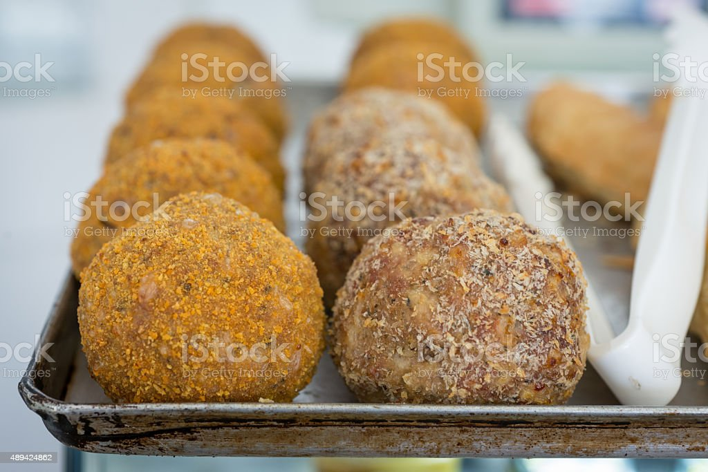 Scotch eggs on a baking tray with tongs stock photo