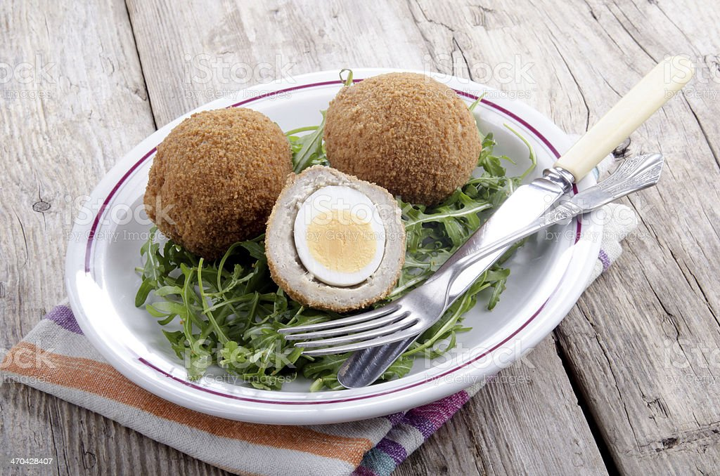 scotch eggs on a plate with rocket salad stock photo