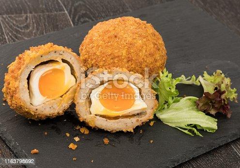 Runny Scotch eggs on a cutting board
