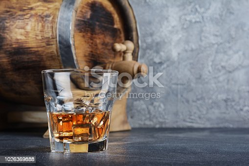 Strong alcoholic drink scotch whisky with ice cubes in old fashion glass and vintage wooden barrel in cellar on gray concrete background