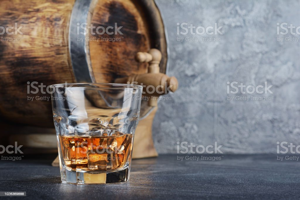 Scotch whisky with ice cubes in old fashion glass and vintage wooden barrel stock photo